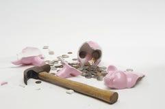 Brutna Piggybank med hammaren och mynt Arkivbilder