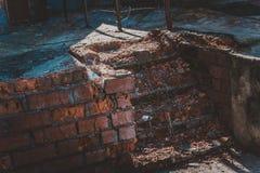 Brutna stentegelstenmoment som delvist är bevuxna med gräs arkivfoton