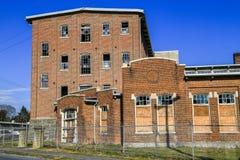 Brutna Windows på fabriksbyggnad Arkivbild