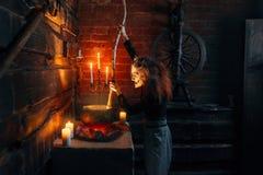 A bruxa assustador que cozinha a sopa e lê o período foto de stock royalty free