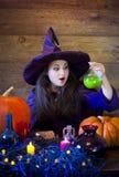 Bruxa bonita em Dia das Bruxas roxo com uma vassoura Fotografia de Stock