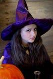 Bruxa bonita em Dia das Bruxas roxo com uma vassoura Imagens de Stock