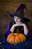 Bruxa bonita em Dia das Bruxas roxo com uma vassoura Imagem de Stock