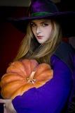 Bruxa bonita em Dia das Bruxas roxo com uma vassoura Imagem de Stock Royalty Free