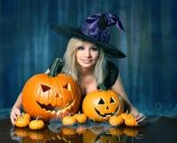 Bruxa com abóboras de Dia das Bruxas Louro bonito feliz Fotografia de Stock