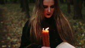 Bruxa com um livro e velas na floresta vídeos de arquivo