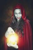 Bruxa de Dia das Bruxas com a bola de fogo em suas mãos imagem de stock royalty free