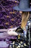 Bruxa de Dia das Bruxas com uma mágica em uma jovem mulher bonita da floresta escura nas bruxas chapéu e traje que guardam a luz  fotografia de stock