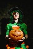 A bruxa de Dia das Bruxas guarda uma abóbora alaranjada fotos de stock