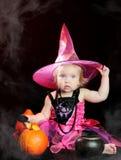 Bruxa do bebê de Halloween com uma abóbora cinzelada imagens de stock