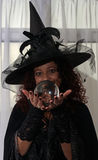 Bruxa moreno bonita que guarda a bola de cristal Imagens de Stock Royalty Free