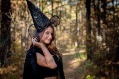 Bruxa nas madeiras, uma moça de Dia das Bruxas em um terno do ` s da bruxa imagens de stock