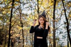 Bruxa nas madeiras, uma moça de Dia das Bruxas em um terno do ` s da bruxa imagem de stock royalty free
