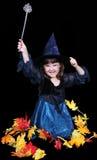 Bruxa pequena do divertimento cercada pelas folhas douradas. Imagens de Stock