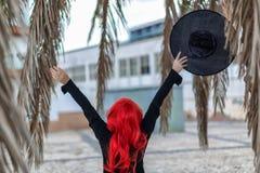 A bruxa pequena em um vestido preto com cabelo vermelho está guardando um chapéu Fotos de Stock
