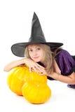 Bruxa que senta-se ao lado das abóboras Imagem de Stock Royalty Free