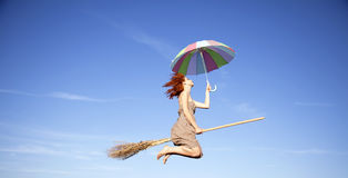 Bruxa red-haired nova no vôo da vassoura no céu imagens de stock royalty free