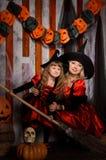 Bruxas de Dia das Bruxas nos trajes com vassoura Fotografia de Stock Royalty Free
