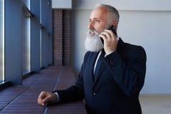 Bryła popielaty mężczyzna opowiada na telefonie podczas gdy opierający na parapecie Obraz Royalty Free