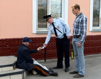 A policeman checks documents from an elderly man on the street. Stock Images