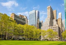 Bryant park, New York, Manhattan. High buildings view from below against blue sky background, sunny day in spring royalty free stock photography