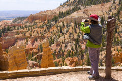 Bryce Canyon Tourist. Female tourist taking a picture of the scenery in Bryce Canyon National Park Royalty Free Stock Images