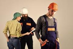 Brygada pracownicy, budowniczowie w hełmach, naprawiacze i dama dyskutuje kontrakt, popielaty tło Rekrutacyjny pojęcie zdjęcie stock
