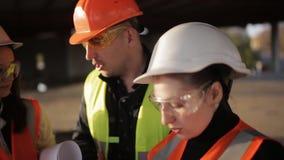 Brygadier transakcje z dwa kobietami od kierowniczego biura o wykonujących terminach dostawa materiały budowlani i pracie zdjęcie wideo