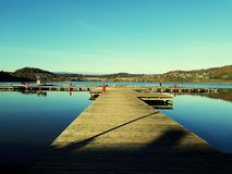 Brygga av wood och blått vatten i en sjö Österrike Arkivbild