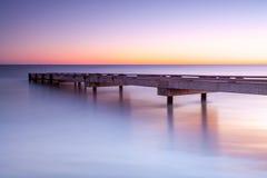 Brygga i soluppgången med stilla havsvatten Arkivbilder