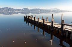 Brygga på sjön, lugna vattnen och reflexionen Arkivbilder
