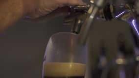 Bryggare som häller mörkt öl till exponeringsglas från klappet i bryggeri Slut upp bartenderhänder som häller kraftigt öl till ex arkivfilmer