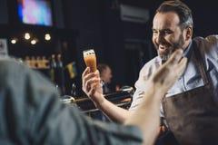 Bryggeriarbetare med exponeringsglas av öl Arkivbilder