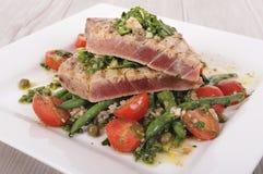 Brynt tonfiskbiff med böna- och tomatsallad Fotografering för Bildbyråer