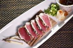 Brynt tonfisksashimi på den vita plattan Arkivfoto