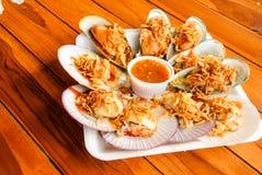 Brynte kammusslor och musslor med kryddig havs- sås Royaltyfri Foto