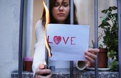 bryt upp slutet av förälskelsebegreppet kvinna som bränner ett papper med ordförälskelsen Arkivbilder