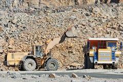 Bryta för granit Rulla laddarpäfyllningsmalm in i dumper på dagbrotts- royaltyfri bild