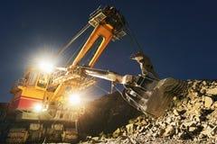 Bryta konstruktionsbransch Grävskopa som gräver granit eller malm i villebråd arkivbild