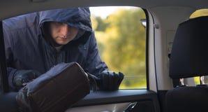 Bryta lagen, drar rånaren påsen ut ur bilfönstret arkivbilder