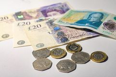 Brytyjska funtowa moneta na Brytyjskiego funta banknotach Fotografia Stock