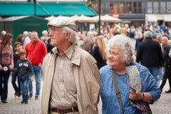 BRYUGGE BELGIEN - SEPTEMBER 07, 2017: Ett äldre lyckligt gift par av turister som reser längs en upptagen gata Arkivbild