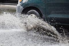 Bryzga samochodem gdy ono iść przez wody powodziowej Fotografia Stock