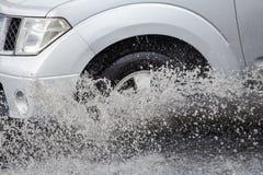 Bryzga samochodem gdy ono iść przez wody powodziowej Obrazy Stock