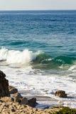 Bryzgający falę na backwash i piaskowatej plaży z głazami i piaskiem, obrazy stock