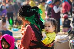 Brzęczenia Giang Wietnam, Feb, - 14, 2016: Hmong mała dziewczynka na jej matce z powrotem w lokalnym rynku w Dong Van Okręg zdjęcie royalty free