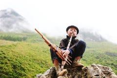 BRZĘCZENIA GIANG, WIETNAM, Listopad 14th, 2017: Hmong młodzi człowiecy bawić się tradycyjnego instrument, północny Wietnam obraz stock
