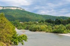 Brzeg halny rzeczny Ashe z zielonymi drzewami, górami i niebem przy tłem, Krasnodar region, Adygea, Rosja obrazy royalty free