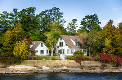 Brzeg jeziora domy i Colourful jesieni drzewa obrazy stock