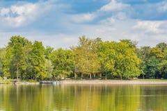 Brzeg jeziora krajobraz z pięknymi drzewami i łodziami w słońcu Zdjęcie Stock